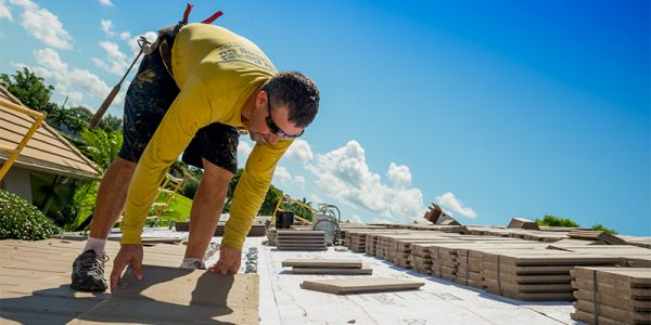 man on roof completing tile roofing services | Gulf Coast Roofing | Naples, Florida